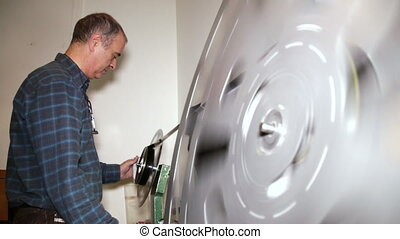 Film Technician Rewinding 35mm Film - A technician rewinds...