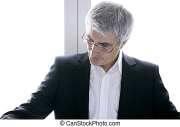 businessman senior gray hair looking down to his work desk