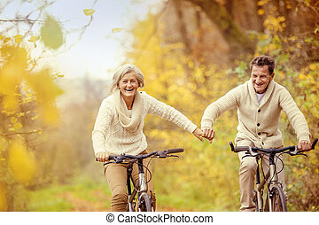 Active seniors riding bike in autumn nature. They relax...
