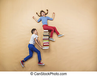Children with books - Happy children playing with group of...
