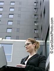 Businesswoman with laptop computer on the city, buildings on...