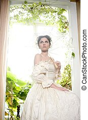 Victorian beautiful woman, white dress at home window with...