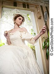 Victorian beautiful woman, white dress at home looking hand...