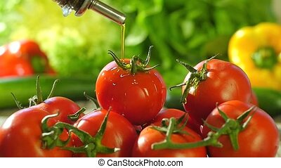 pouring olive oil over tomatoes - fresh tomatoes and olive...