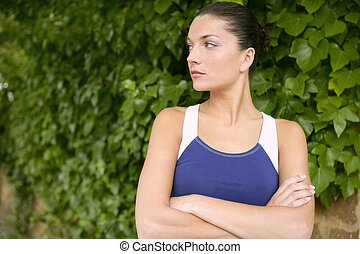 Beautiful sport woman portrait over green leaves