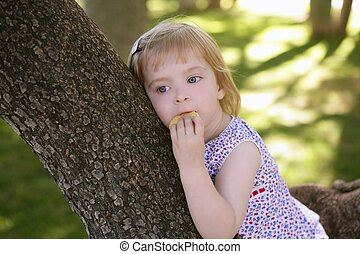 Beautiful little girl eating biscuit over tree