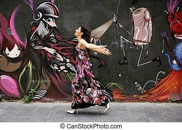 Elegant fashion woman running over urban graffiti
