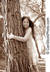 Teen girel hug a tree trunk, pine forest