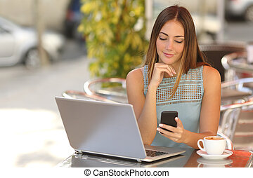 Self employed woman working with her phone and laptop in a...