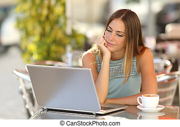 Woman watching a laptop in a restaurant - Serious woman...