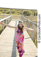 One teen girl running outdoor at the park, hippy pink dress
