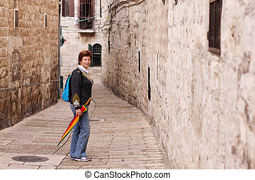 Happy senior caucasian woman travelling in the streets of...