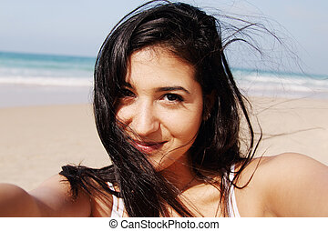 Beautiful girl smiling on the beach with the sand, sea and...