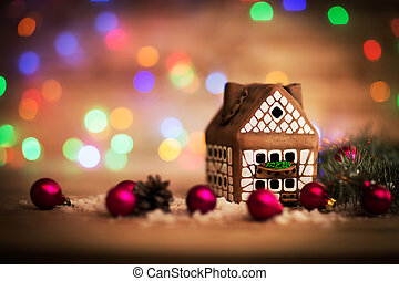 beautiful Christmas house with fir paws on wooden background