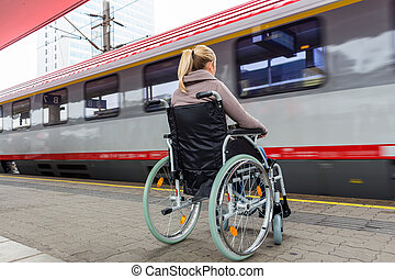 woman sitting in a wheelchair on a train station - a young...