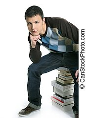 Young student boy sitting over stack books isolated on white