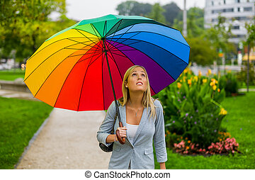 woman with umbrella - a young woman walks with a colorful...