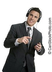 Handsome businessman dancing hearing music with headphones