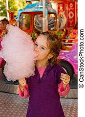 child on kirtag with cotton candy - a girl has fun and...