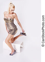 beautyfull blonde fashion woman wearing gold dress and heels...