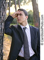 Businessman posing relaxed on a park forest