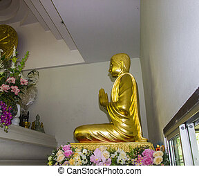 golden monk statue in asian temple monastery