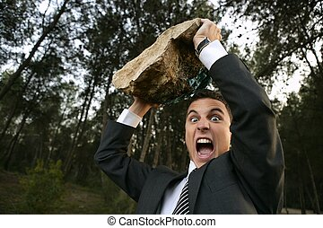 Angry businessman outdoor, big stone in hands - Angry...
