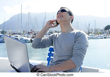 Businessman working with computer on a boat