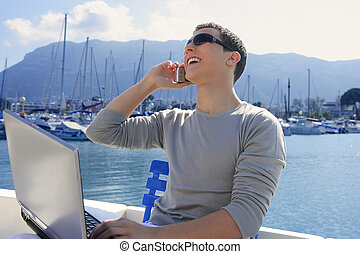 Businessman working with computer on a boat, nice outdoor...
