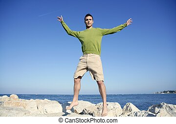 Young man jump over stones in ocean blue shore, sunny summer...