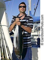 Big game fisherman with saltwater tuna catch in his hands
