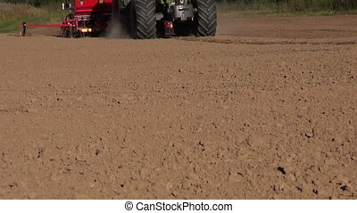 tractor seeding crop grain on field