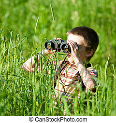 Kid with binocular - Young boy in a field looking through...