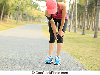 woman runner sports injured knee