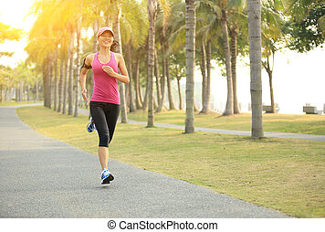 Runner athlete running at tropical park woman fitness...