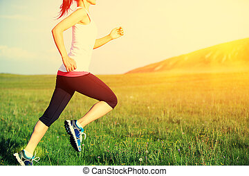 Runner athlete running on grass seaside. woman fitness...