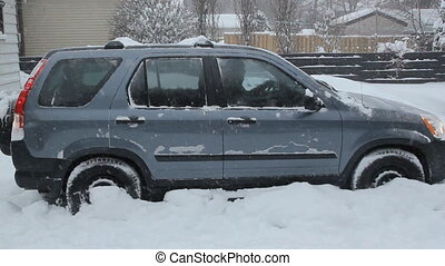SUV backs out of snowy driveway. Snow falling. Winter in...