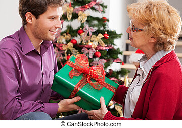 Man giving present - Young attractive man giving present to...