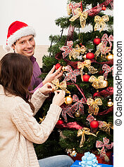 Couple decorating the tree - Young happy couple decorating...