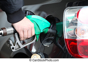 Male Hand Refilling the black Car with Fuel on a Filling...