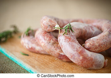Crude homemade beef sausage with a sprig of rosemary