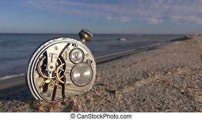 old pocket clock on ocean beach sand