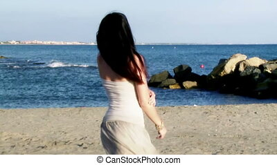 Woman moving long hair slow motion in front of ocean