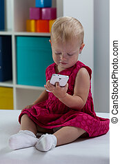 Little girl with smart phone - Little girl in cute pink...