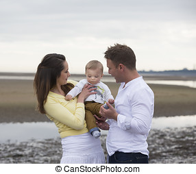 Young Family together on beach.