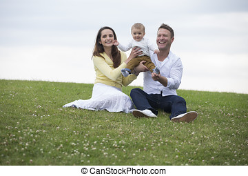 Happy family having fun outdoors Young caucasian family,...