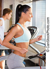 Treadmill workout. Side view of attractive young woman running on a treadmill and smiling with man exercising in the background