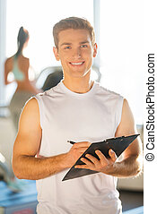 Confident instructor. Handsome young man holding clipboard...