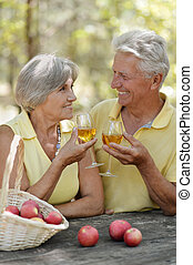 An old couple drinking wine and basket of fruits on the...