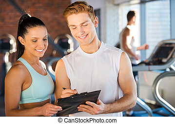 Planning her time in gym. Handsome young male instructor...